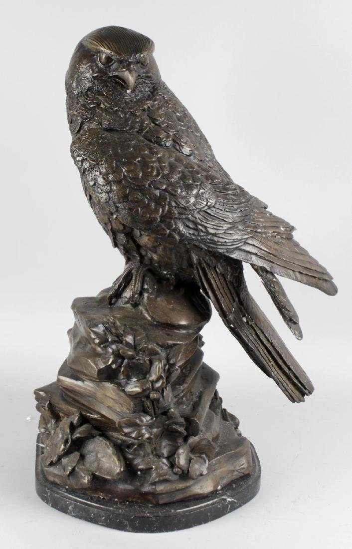 A large modern bronzed figure of a bird of prey.