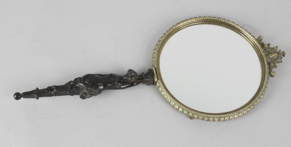 A 19th century lady's bronze hand mirror, the plain