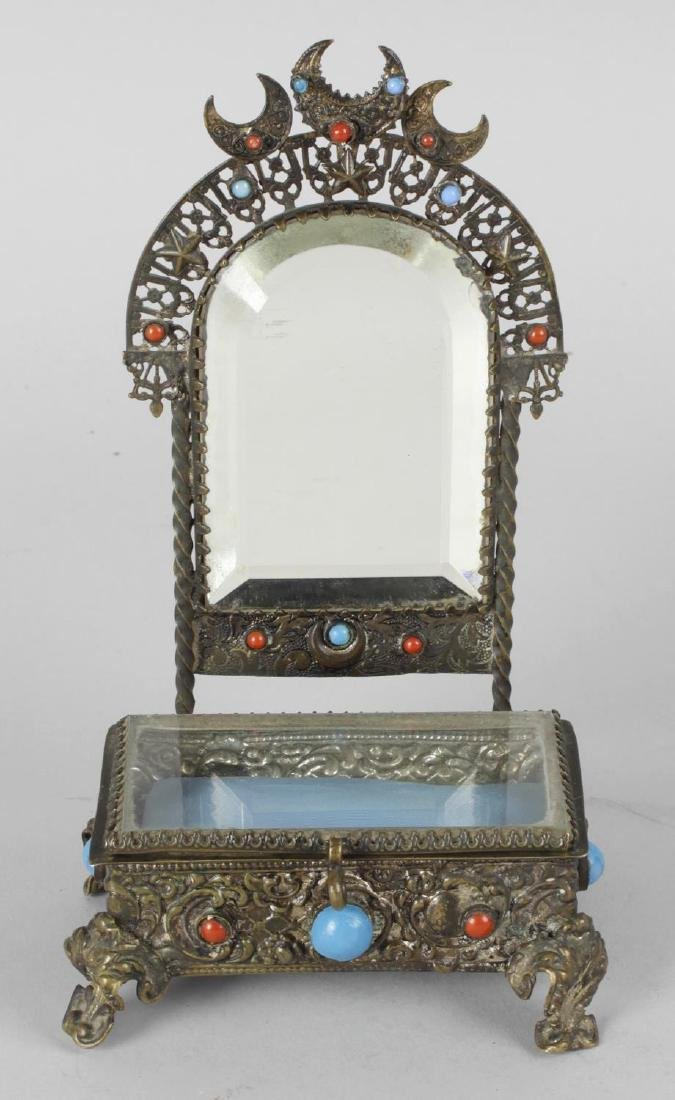A small Eastern metal casket, the hinged glazed opening