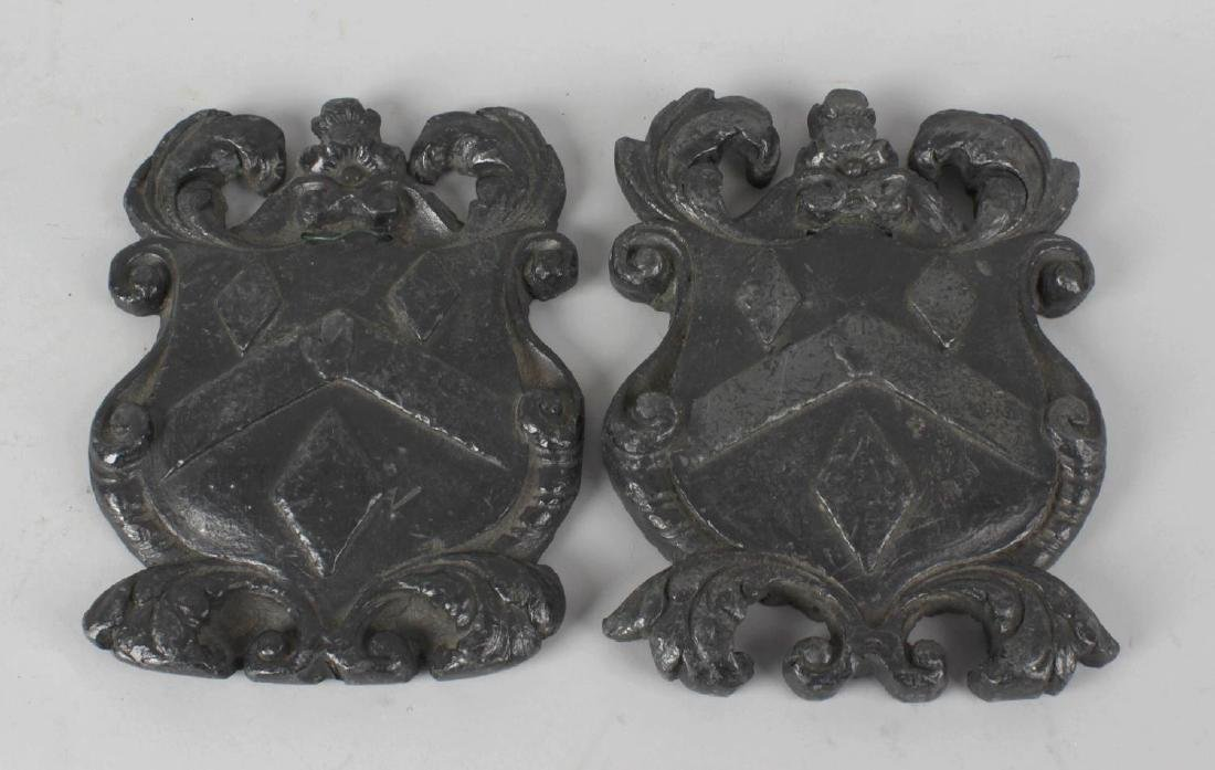 A pair of cast lead plaques, each modelled as a coat of