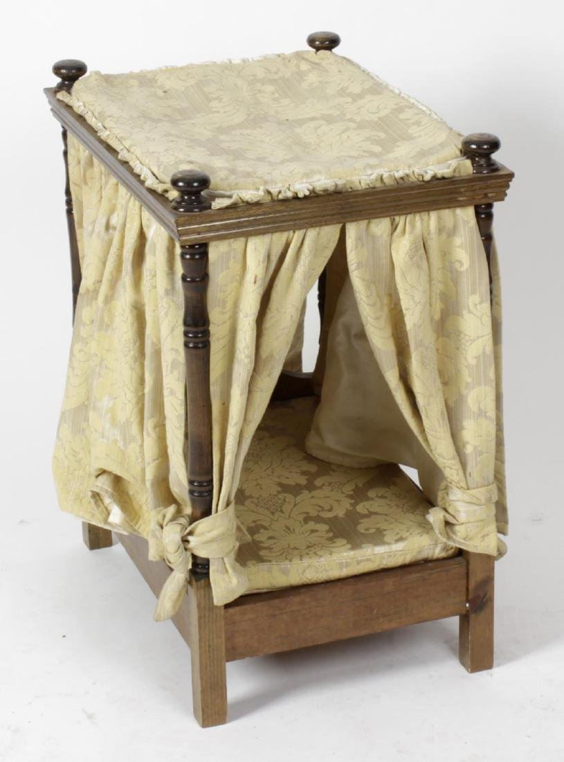 A dolls four poster bed, with turned uprights and
