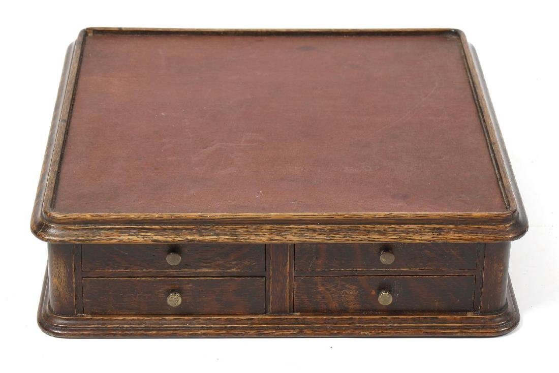 An oak table top cabinet with cloth top, c.1900, one
