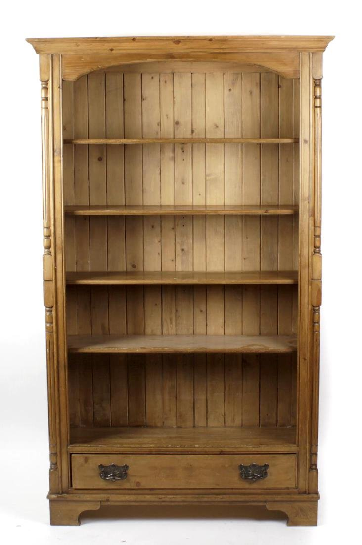 A stained pine open bookcase, the moulded rectangular