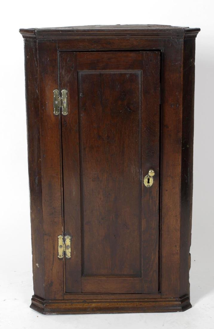 An early George III oak hanging corner cupboard. Circa