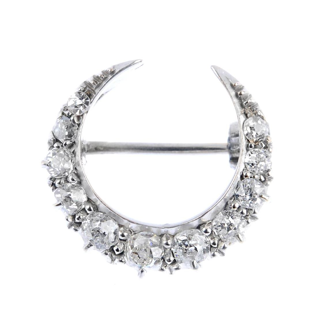 An early 20th century gold diamond crescent brooch.