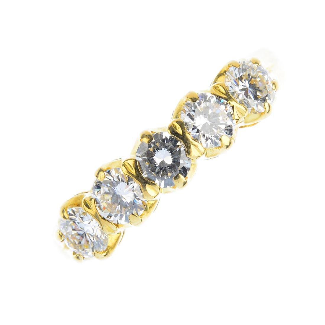 A diamond five-stone ring. The brilliant-cut diamond