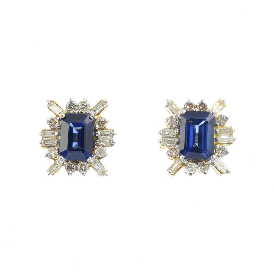 A pair of sapphire and diamond stud earrings. Each