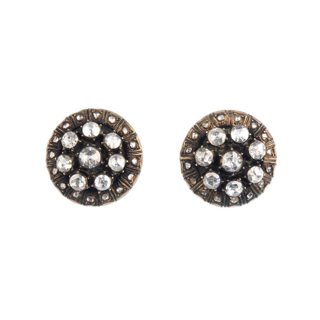 A pair of diamond earrings. Each of circular outline,