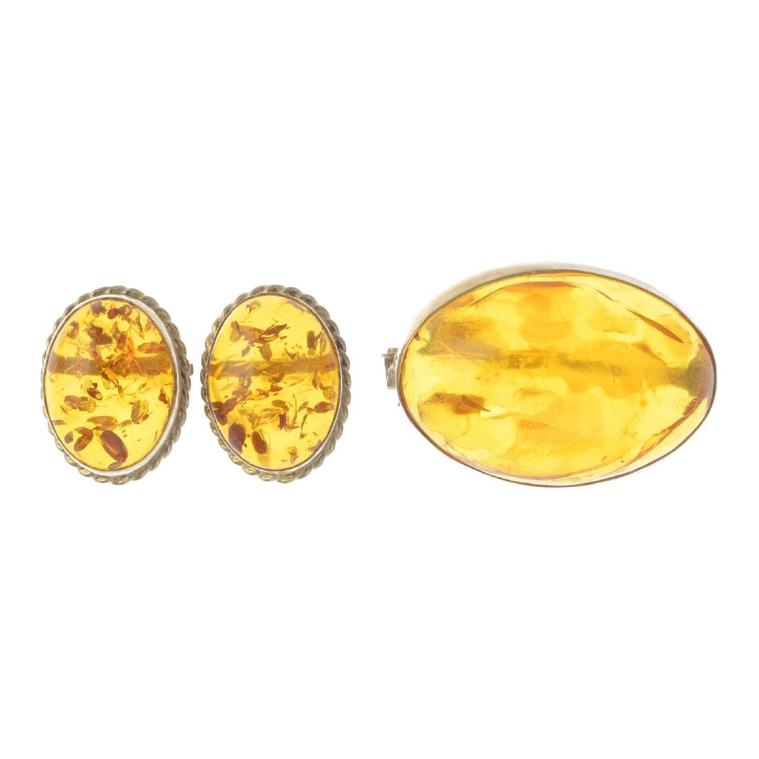 A 9ct gold amber brooch and a pair of earrings. The