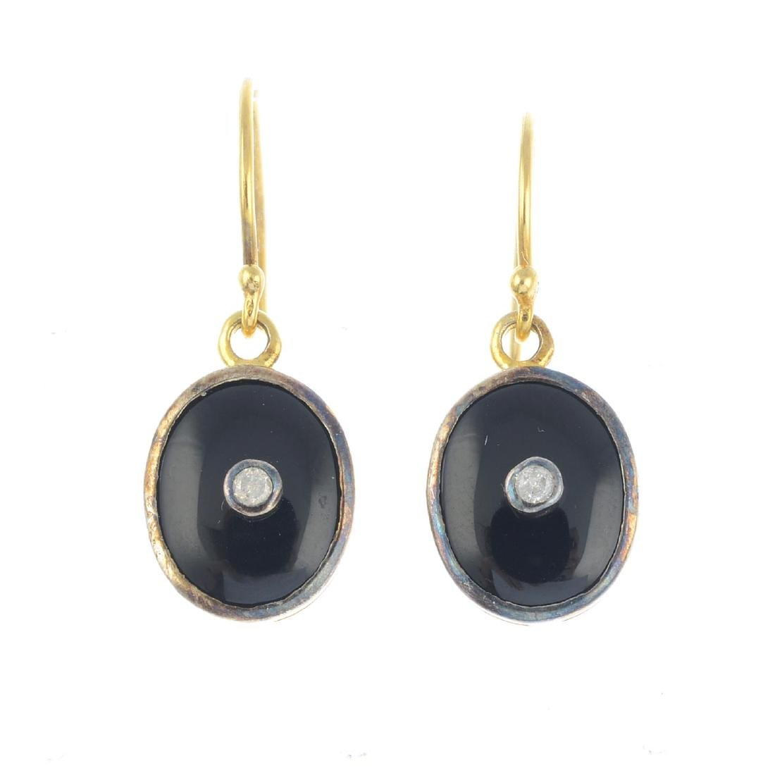 A pair of diamond and onyx earrings. Each designed as a