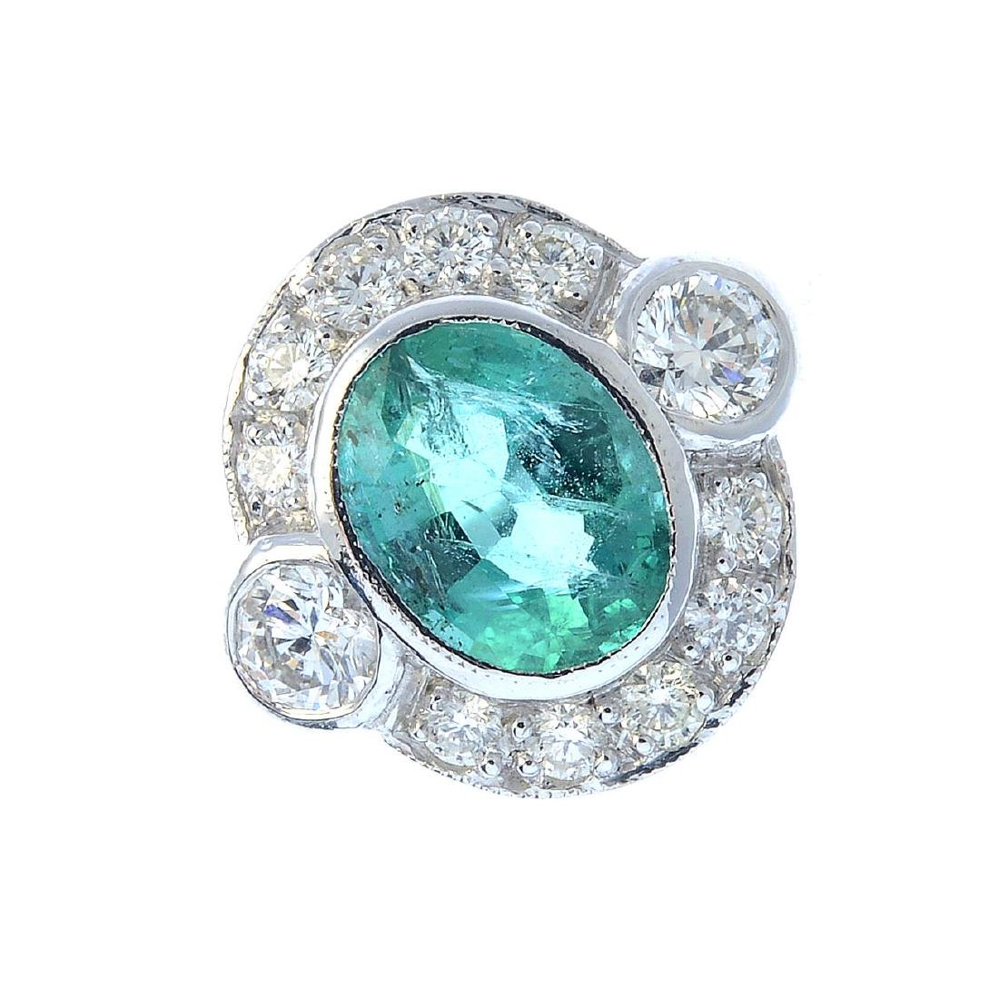 An emerald and diamond dress ring. The oval-shape