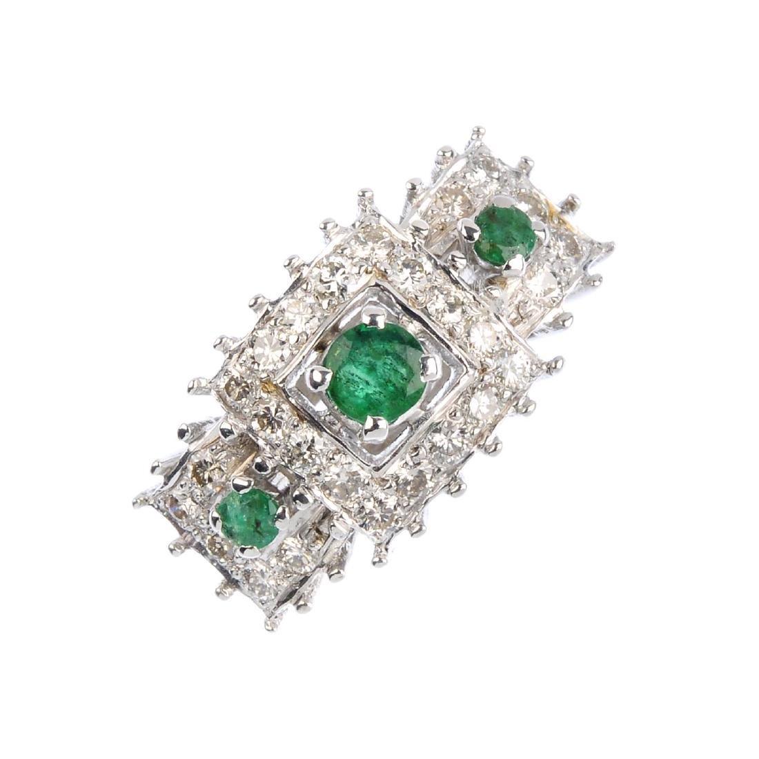 An emerald and diamond dress ring. The circular-shape