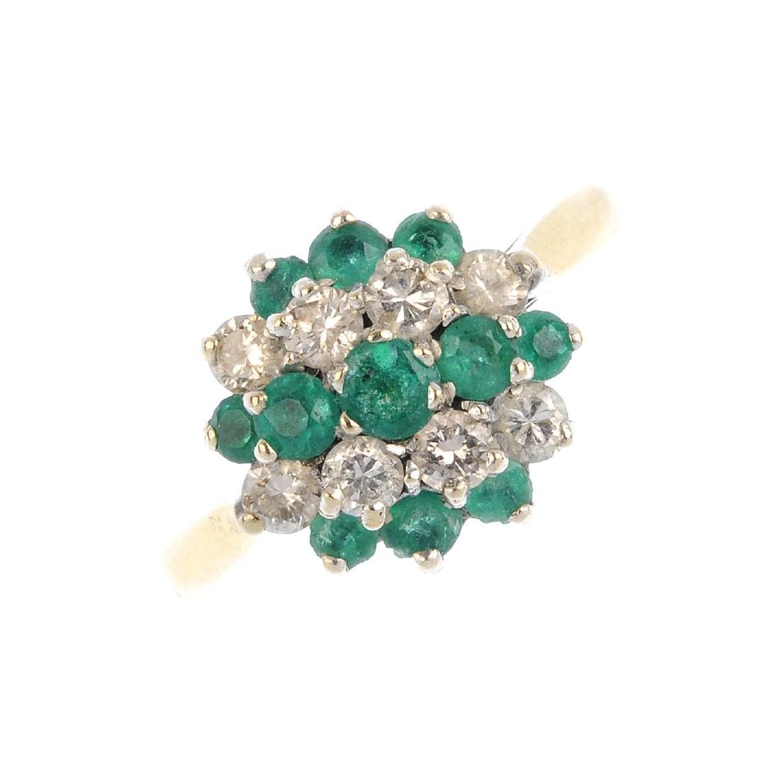 An emerald and diamond cluster ring. Of circular