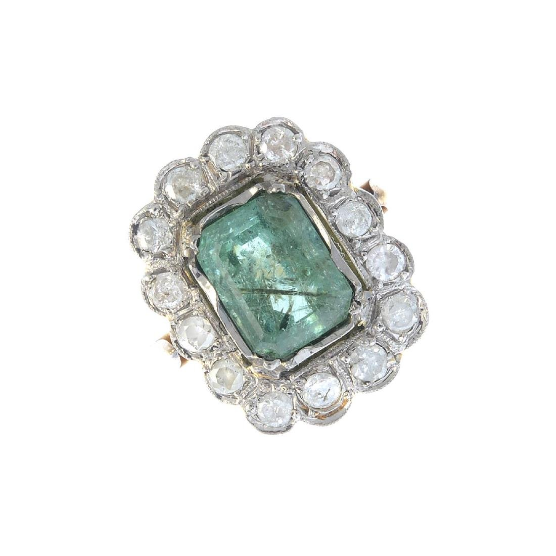 An emerald and diamond cluster ring. The