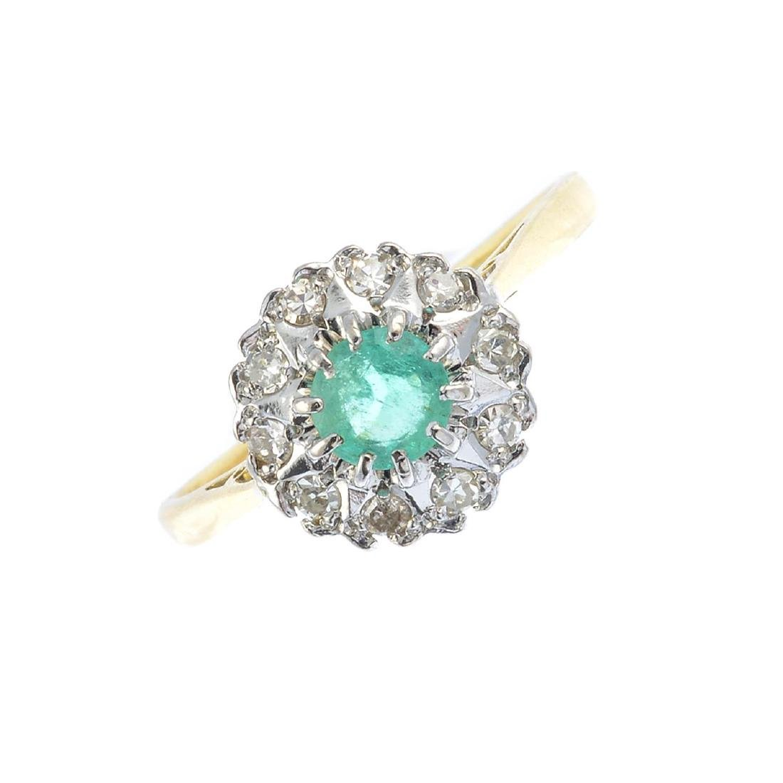 An emerald and diamond cluster ring. The circular-shape