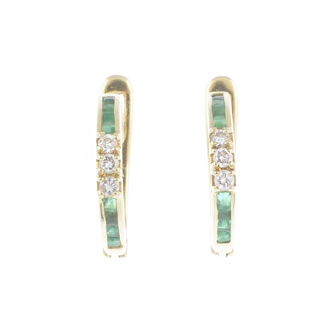 A pair of emerald and diamond earrings. Each designed