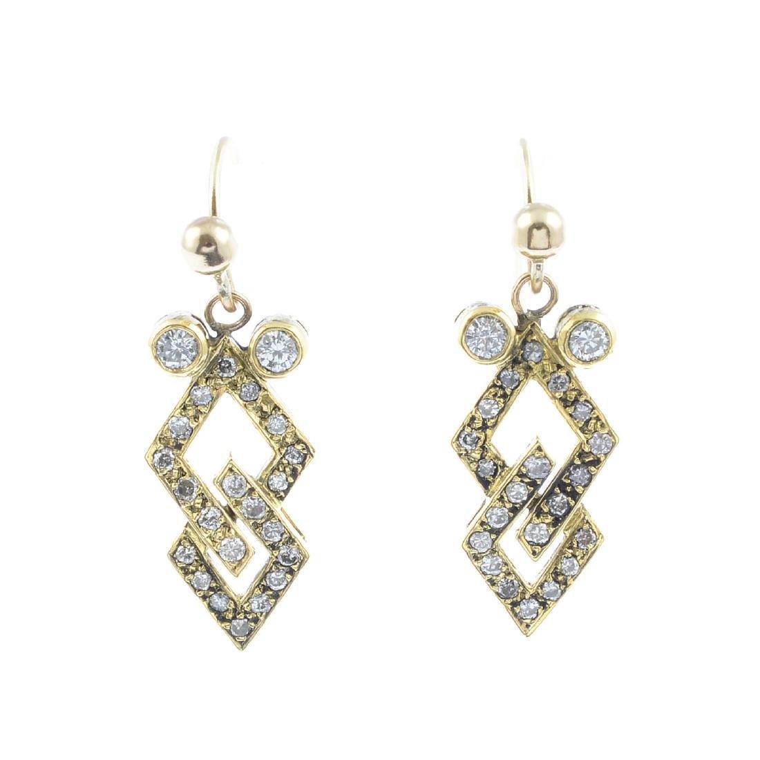 A pair of diamond earrings. Each of geometric design,