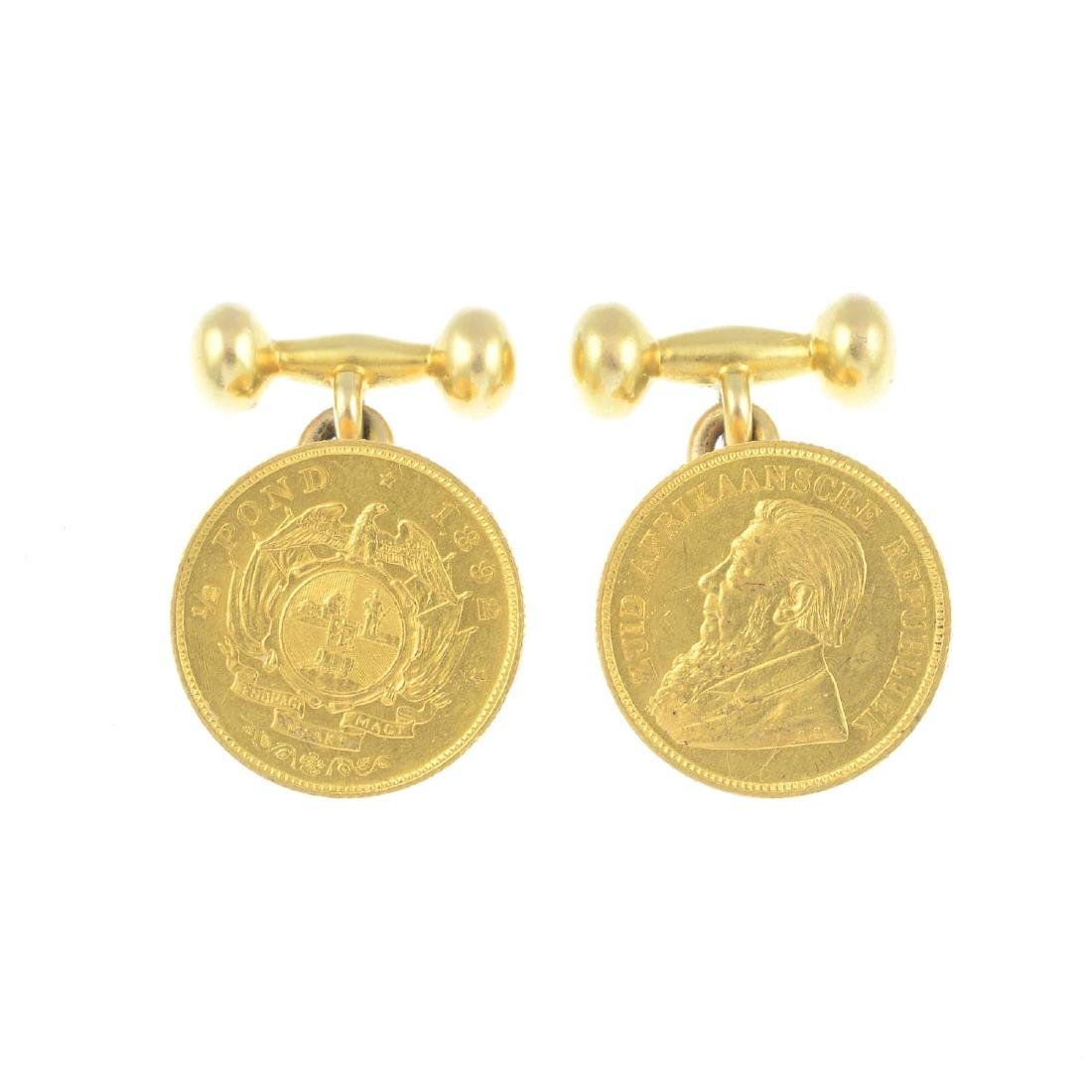A pair of coin cufflinks. Each designed as a South
