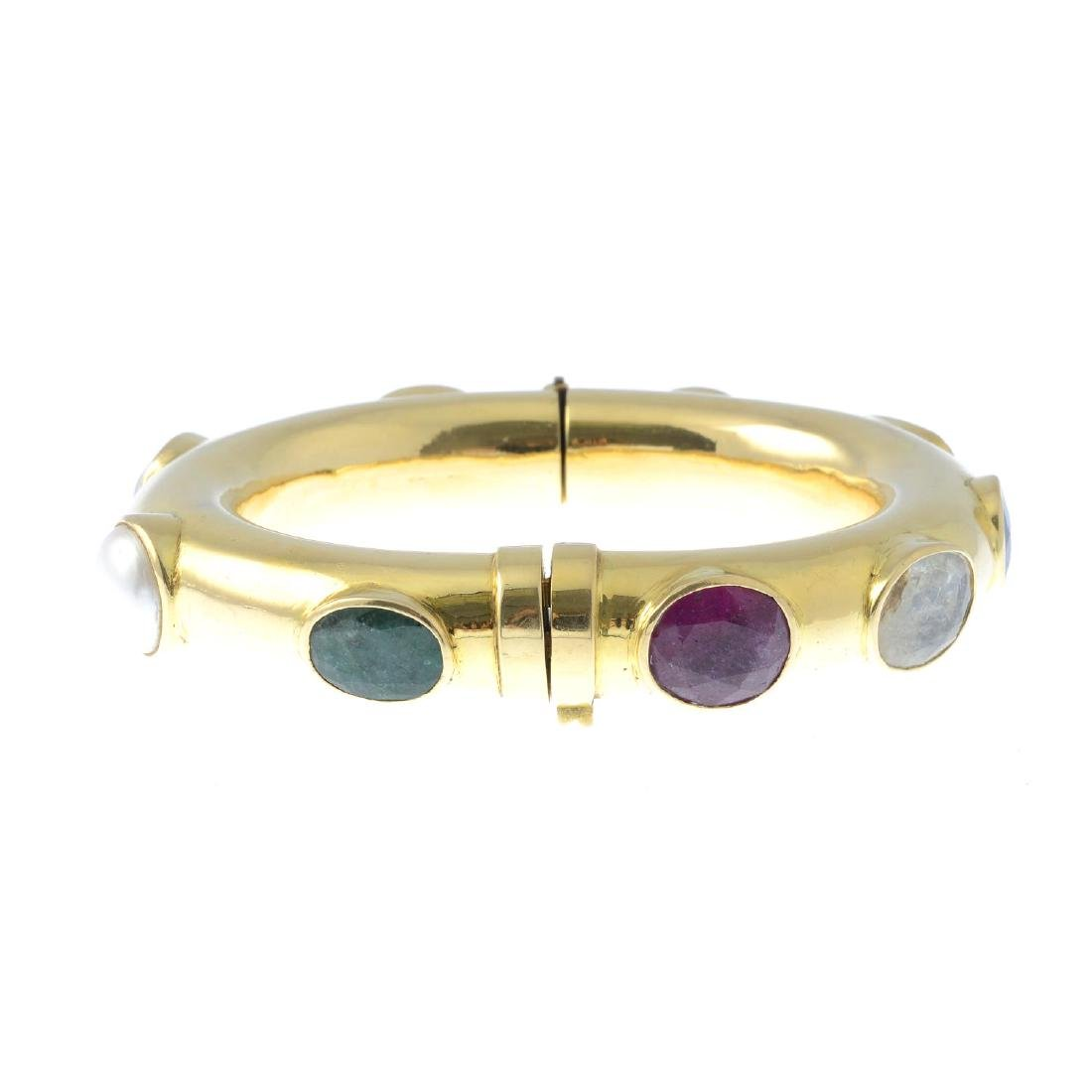 (206711) A gem-set hinged bangle. Inset with vari-gem