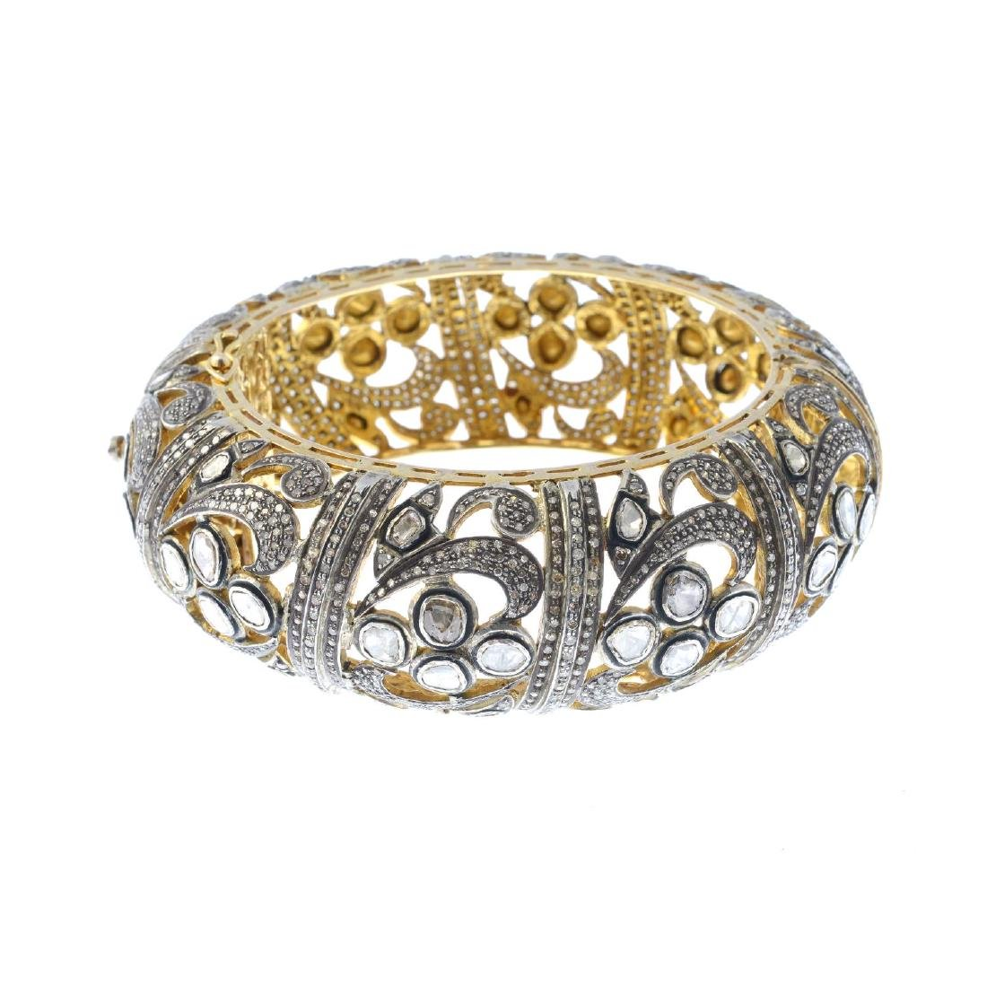(206340) A diamond hinged bangle. Of openwork design,
