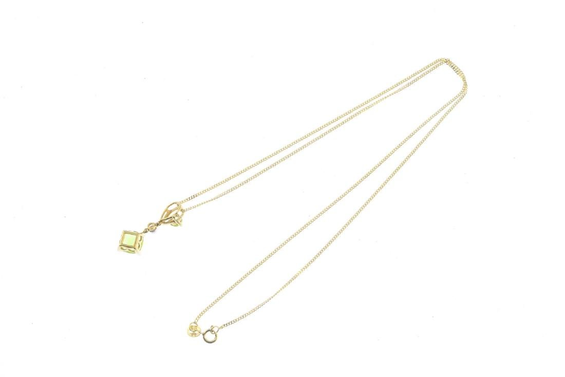 A 9ct gold peridot and diamond pendant. The - 2