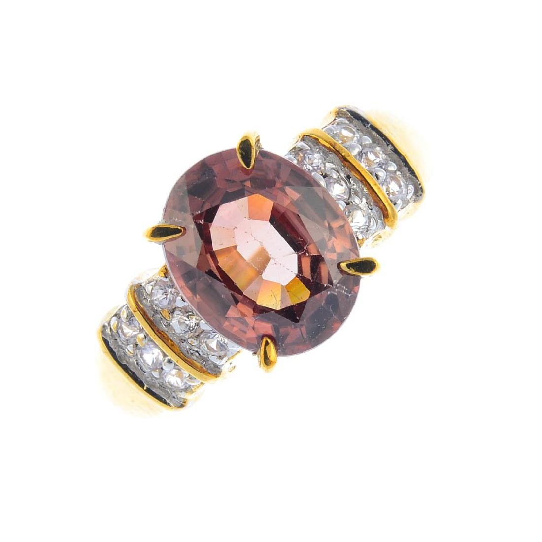 A 9ct gold zircon and diamond ring. The oval-shape