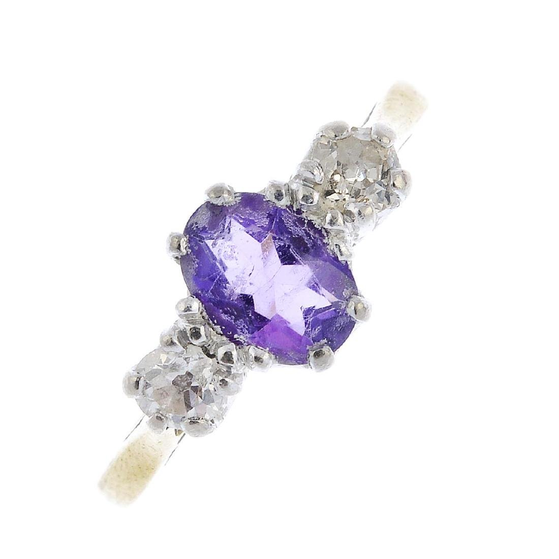 An 18ct gold amethyst and diamond three-stone ring. The