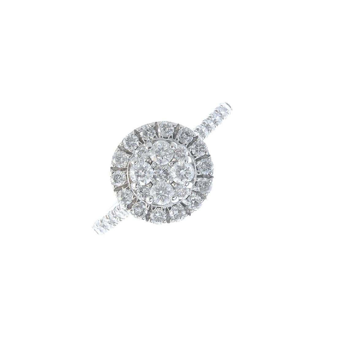 A diamond cluster ring. Of circular outline, the