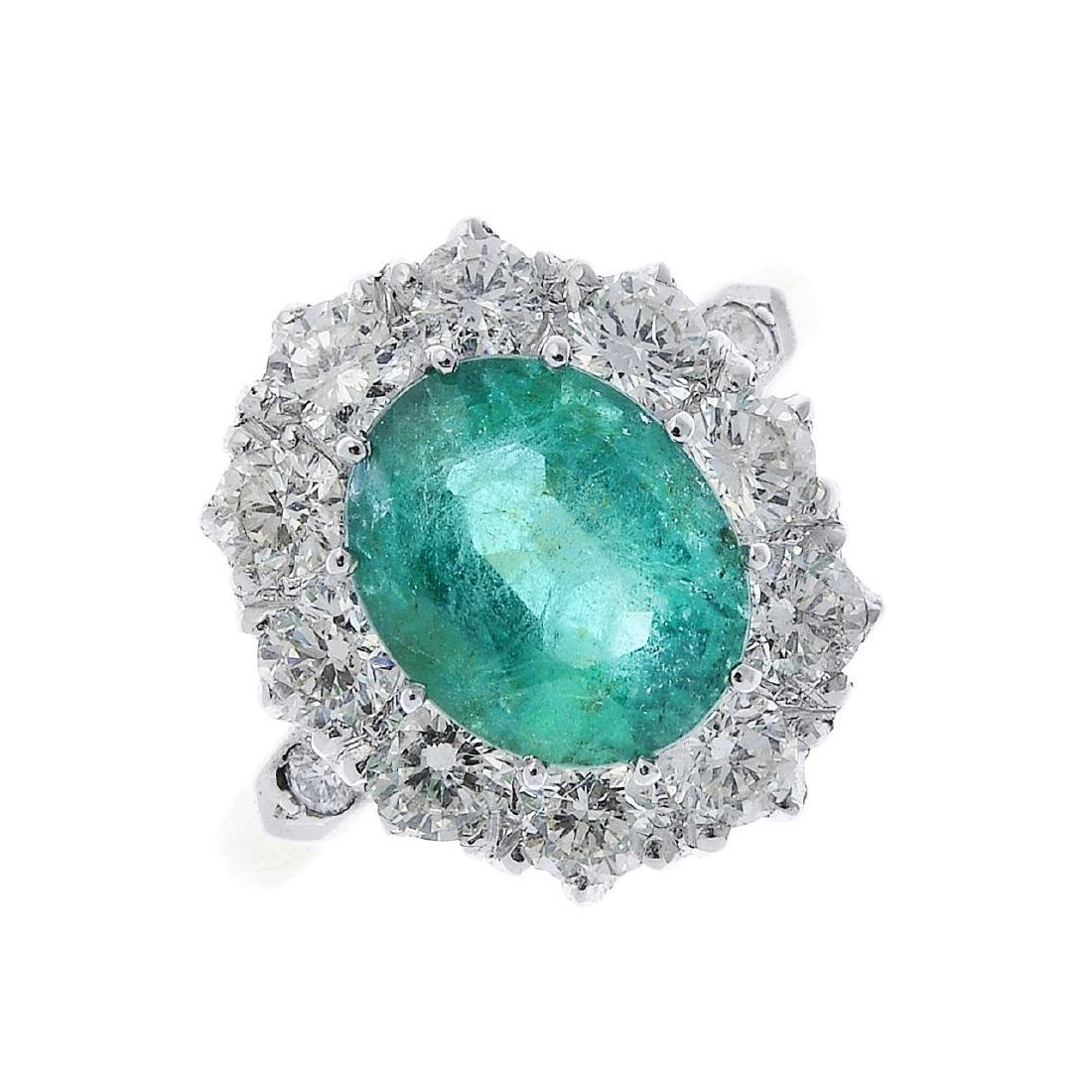 An emerald and diamond cluster ring. The oval-shape