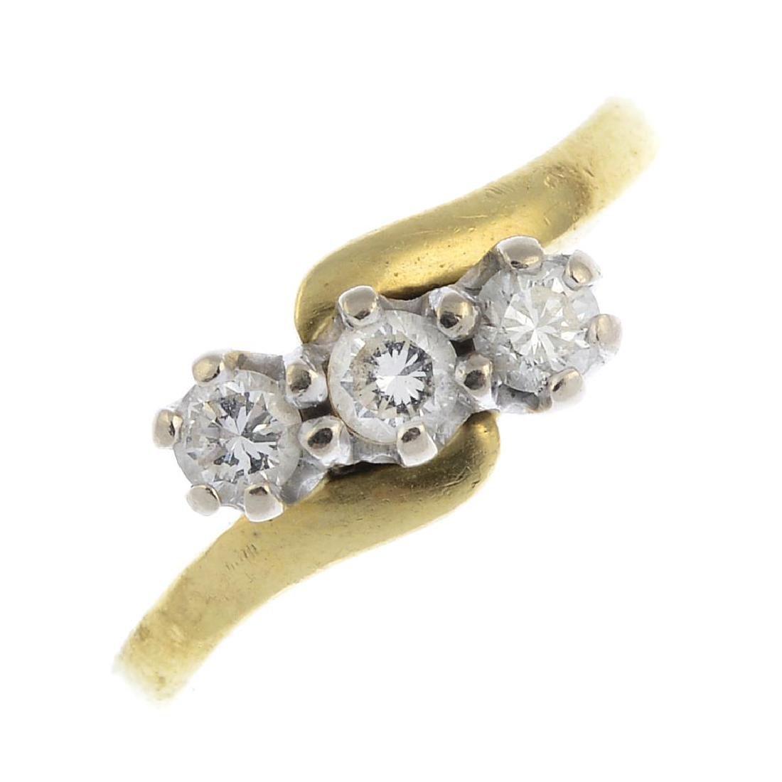 An 18ct gold diamond three-stone ring. The