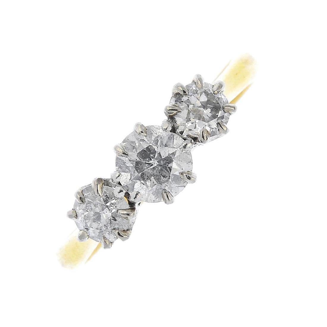 A diamond three-stone ring. The graduated circular-cut