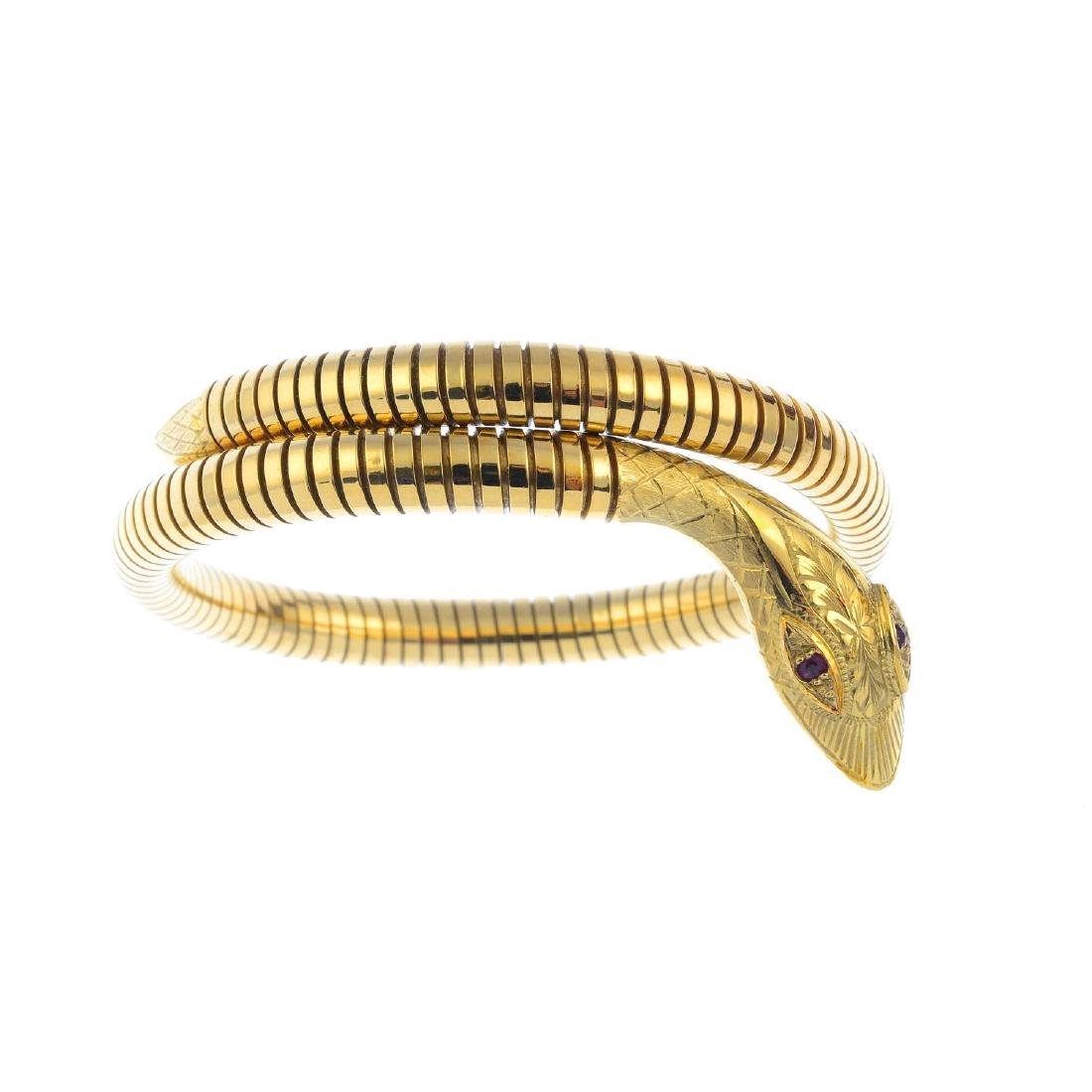 A 9ct gold flexible snake bangle. Designed as a coiled
