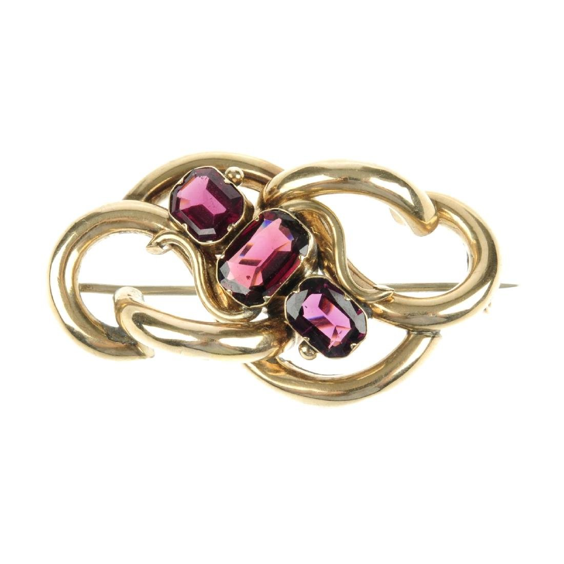 A garnet brooch. Designed as a series of curved