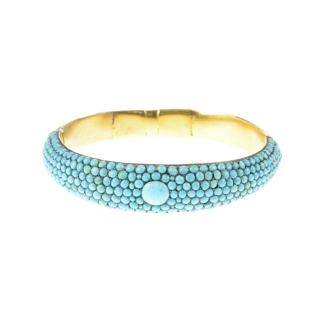 A late Victorian gold and turquoise hinged bangle. With