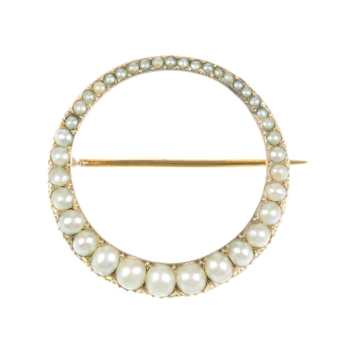 A split pearl brooch. Of open circle design, slimmer to