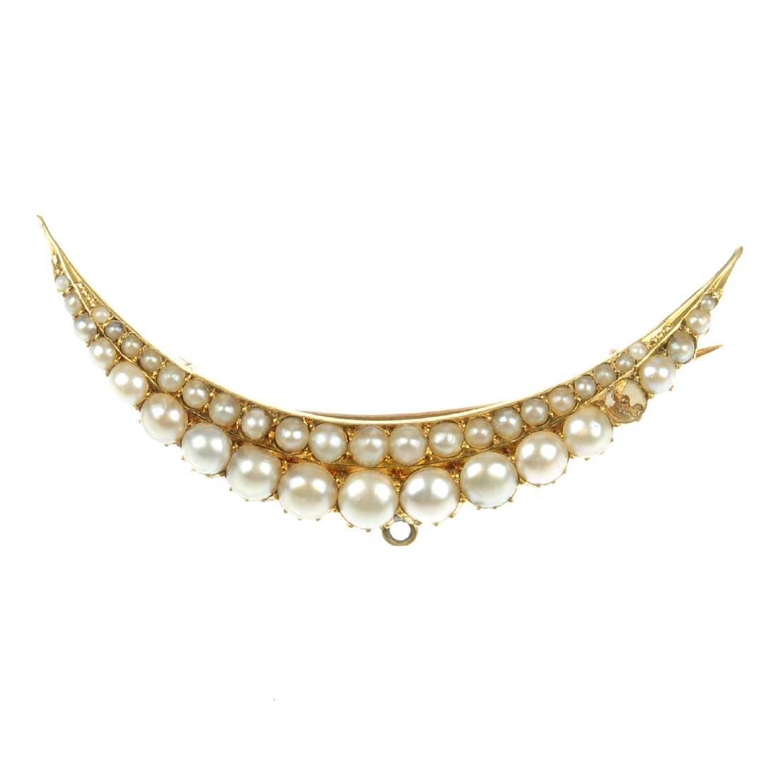 A split pearl brooch. Of crescent shape, designed as
