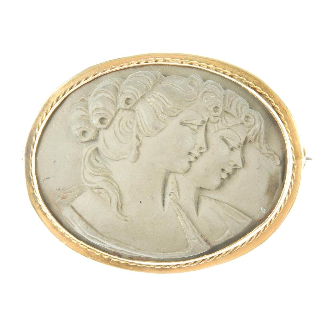 A 9ct gold lava cameo brooch. Of oval outline, the
