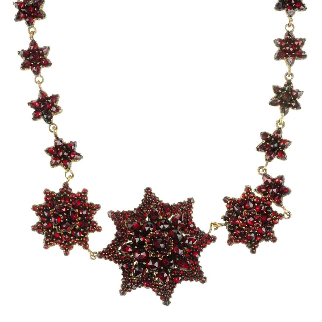 A garnet necklace. Comprising twenty-five star-shape