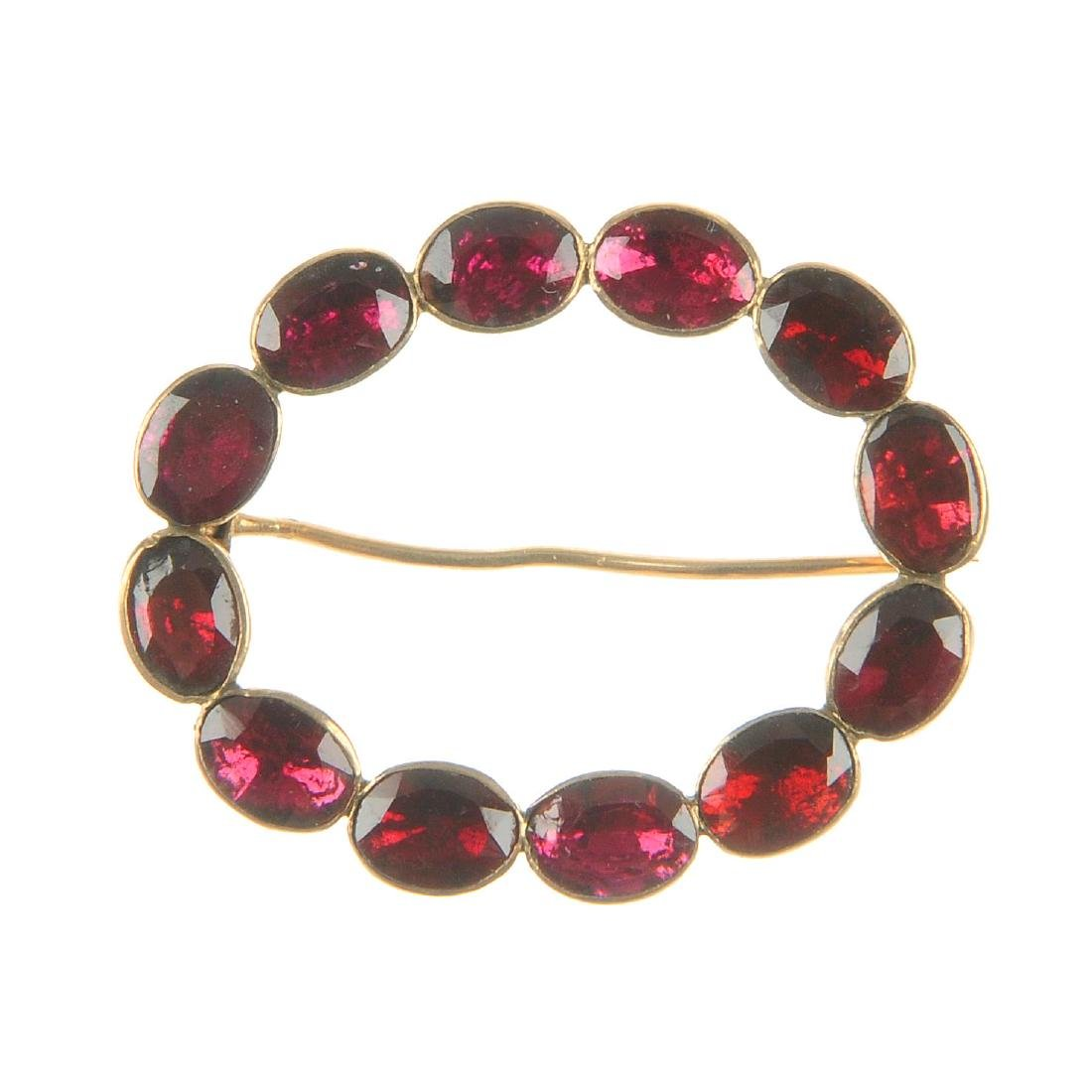 A garnet brooch. The open oval-shape, collet-set with