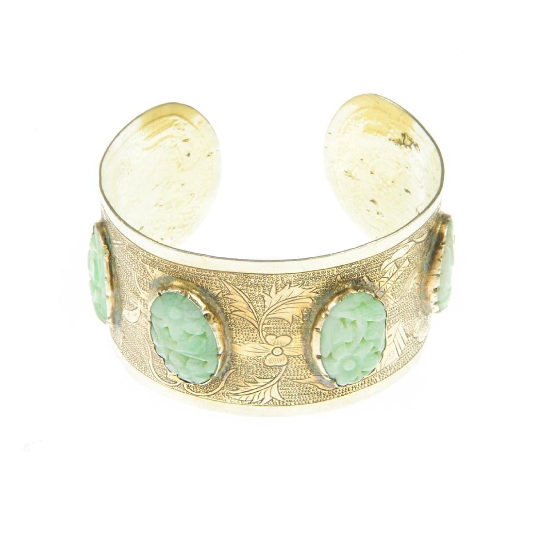 A Chinese bangle with carved jade panels. The open