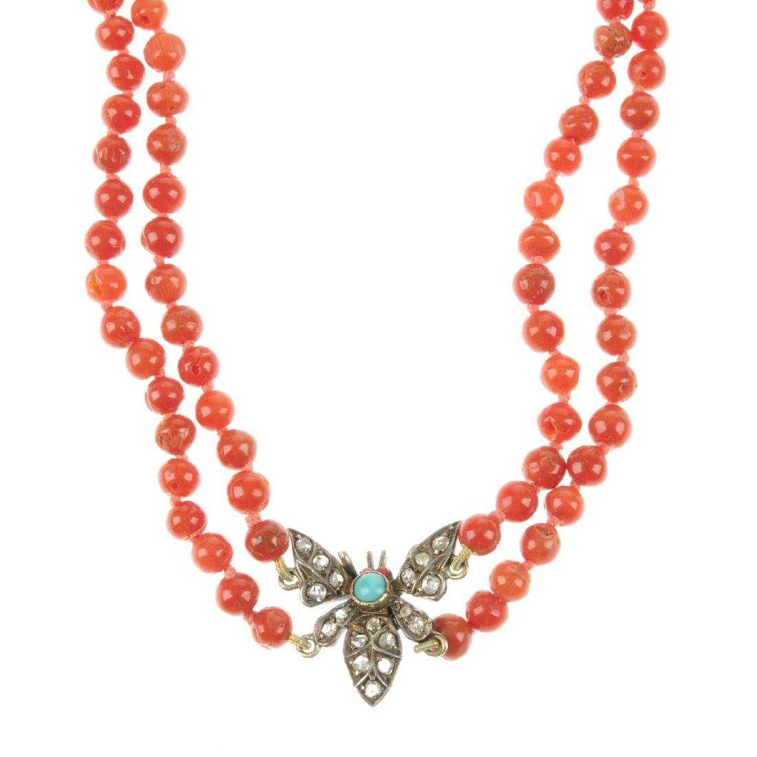 A coral necklace with diamond and turquoise butterfly