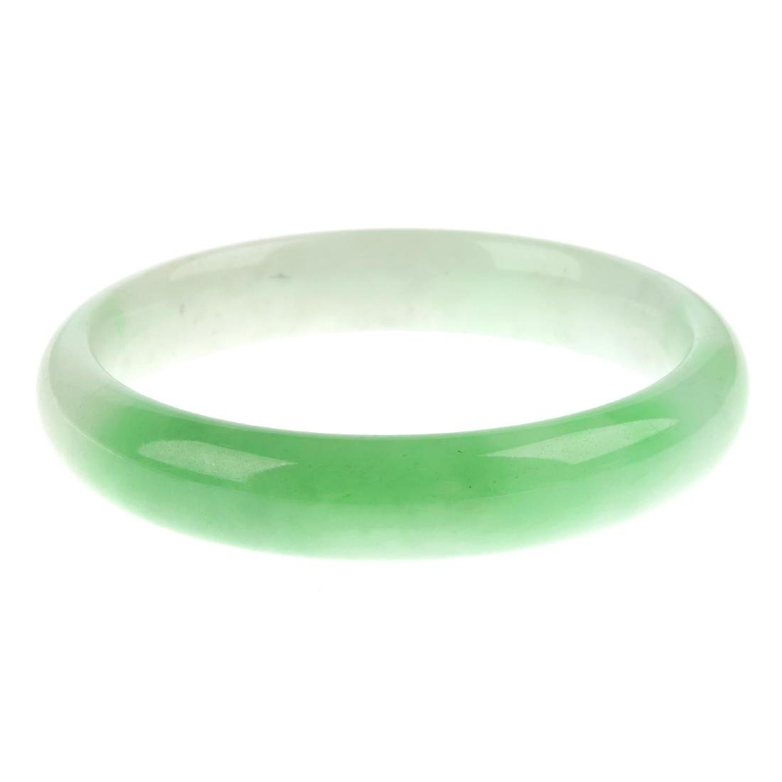 A jade bangle. Of solid design, the bangle with curved