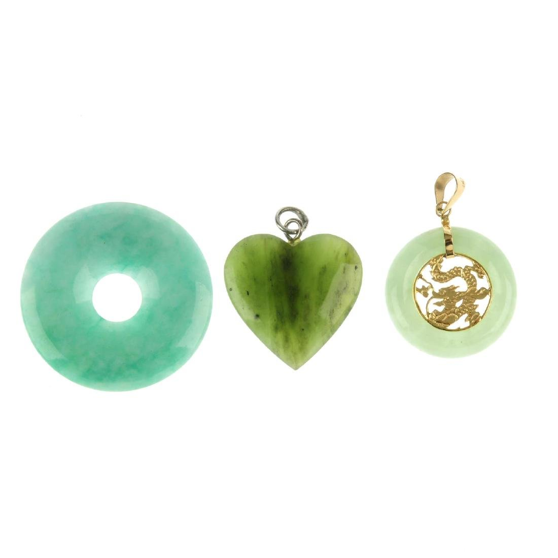 Three jade pendants and a pair of Trifari earrings. The