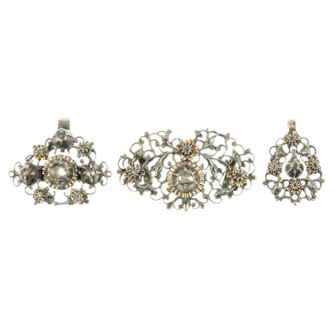 A diamond slider and two diamond pendants. The slider