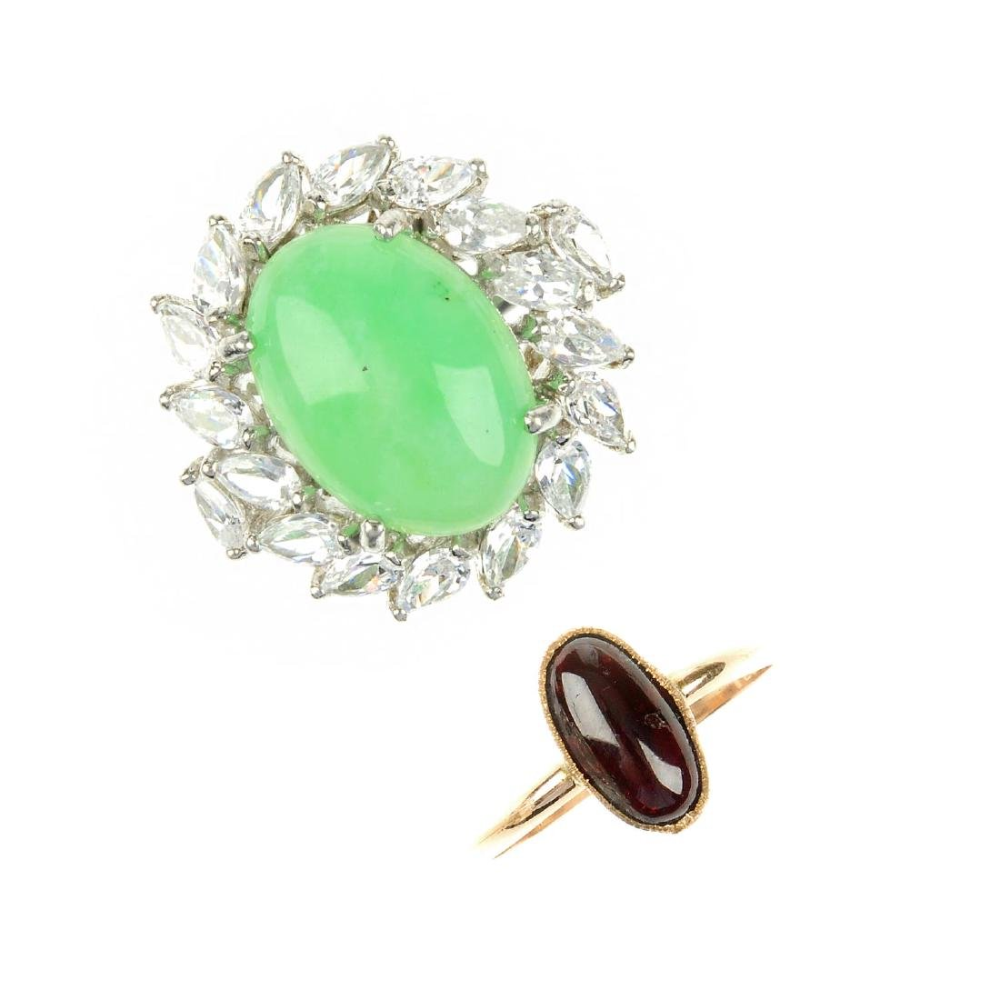 A jade ring, a garnet cabochon ring, a further ring and