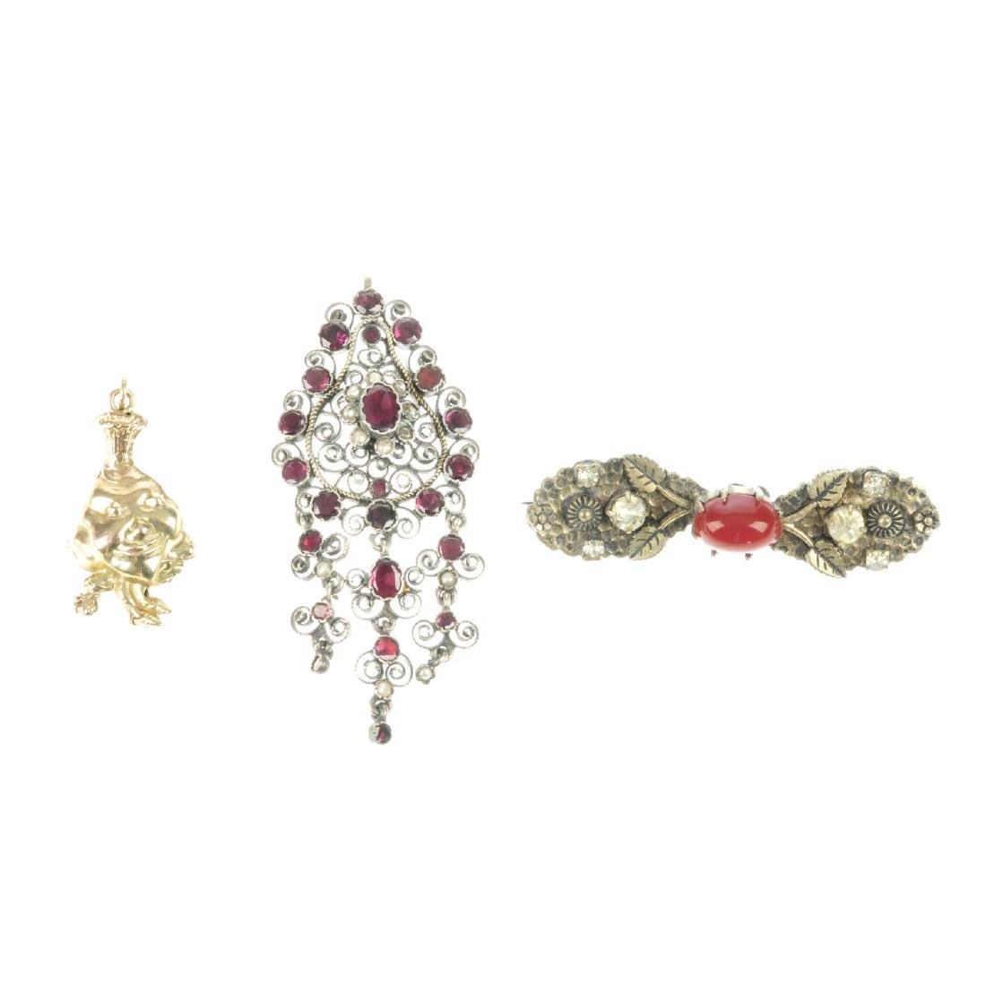 A gem set pendant, a brooch and a 9ct gold charm. The
