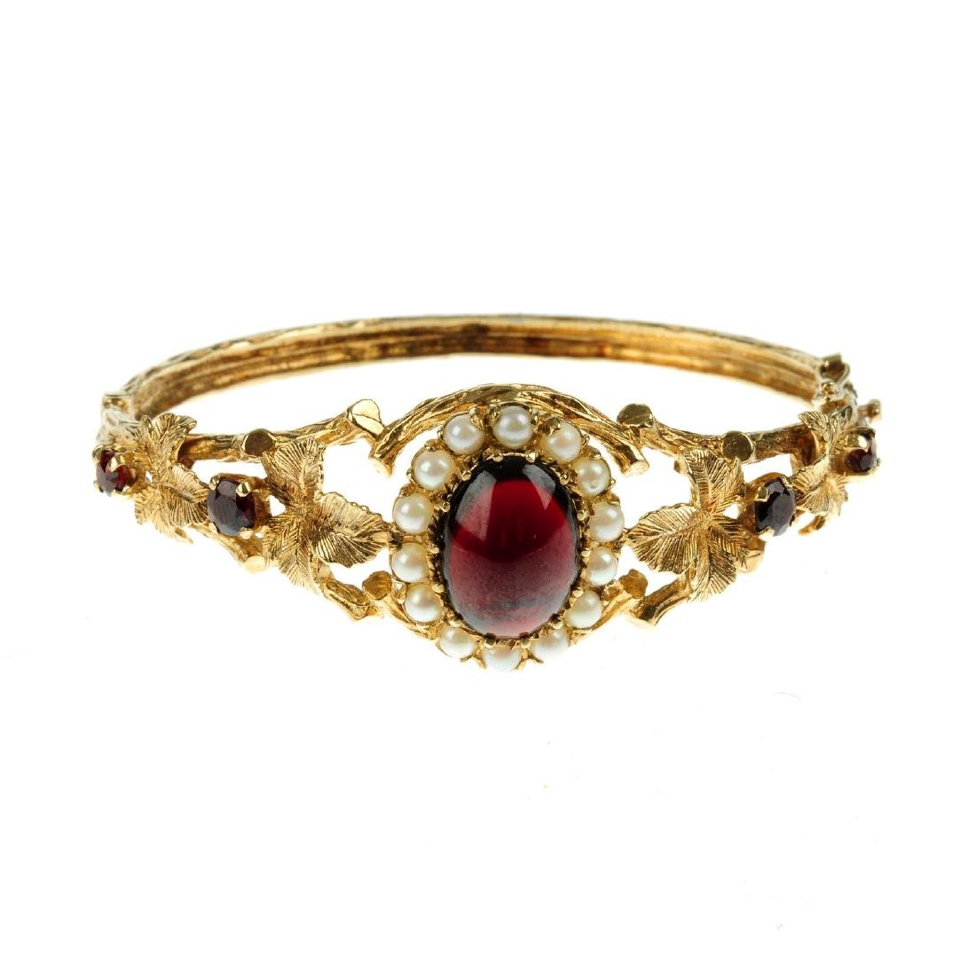 A 9ct gold bangle with red glass cabochon and split