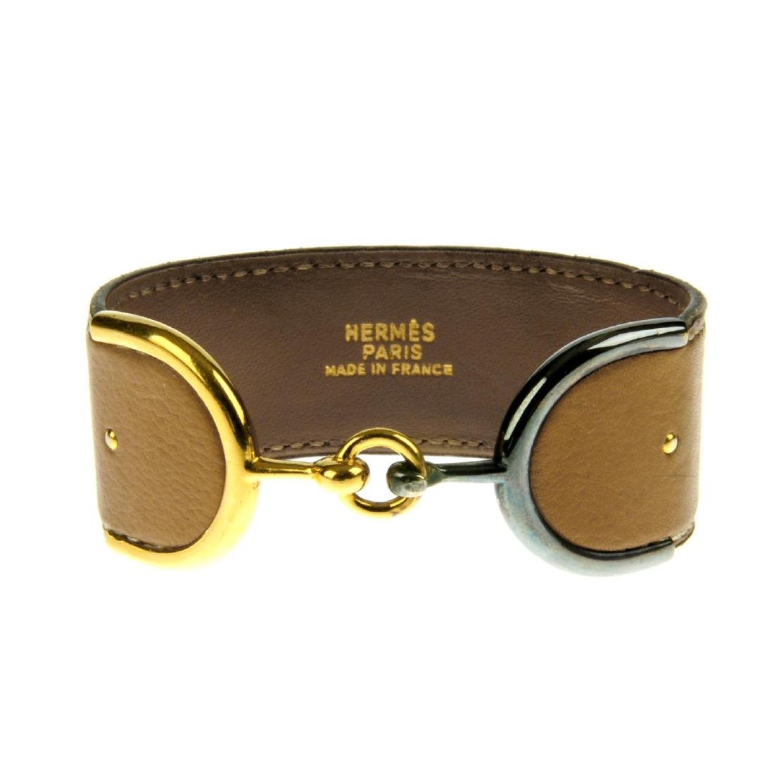 HERMÈS - a bracelet. The tan leather band stitched to