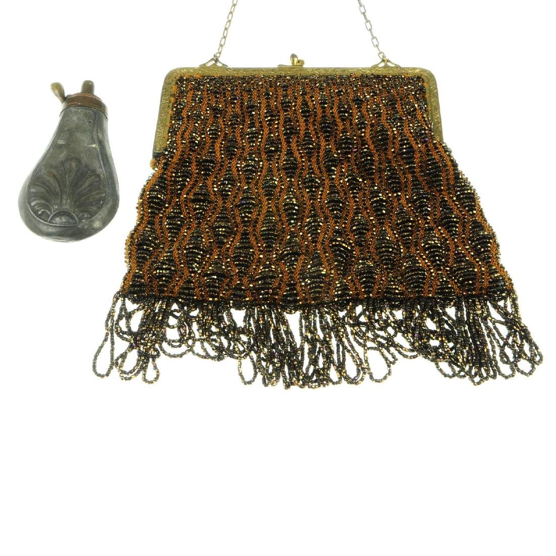 A cut steel evening bag and a gun powder flask. The bag