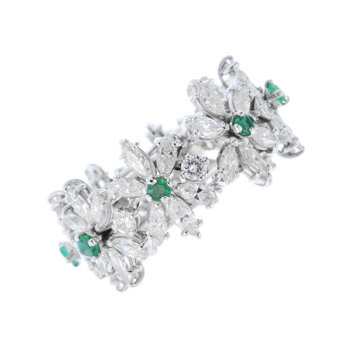 A diamond and emerald floral full eternity ring. Of